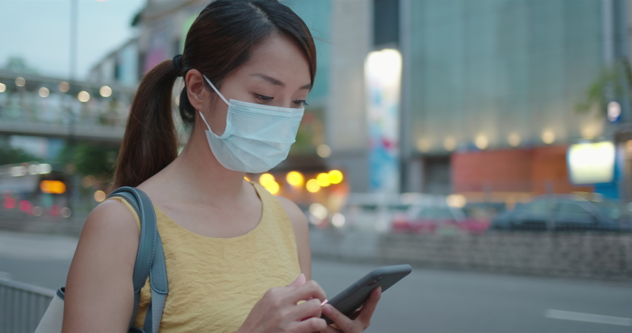 Woman wear face mask and use of mobile phone in city at night   Shutterstock HD Video #1061333812