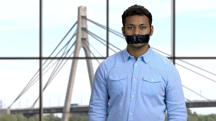 Portrait of Indian man with black tape over mouth. Cables and tower of the suspension bridge on the background. Censorship concept.