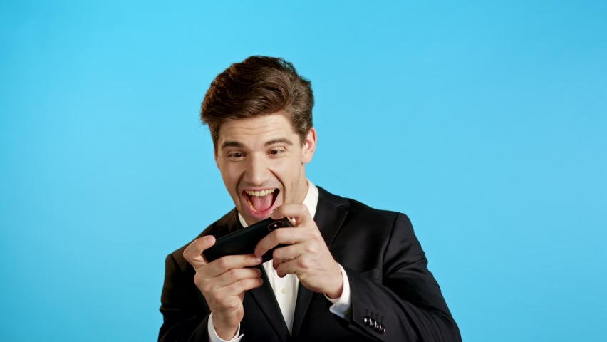 Handsome business man playing game on smartphone on blue studio wall. Using modern technology - apps, social networks. | Shutterstock HD Video #1061339719