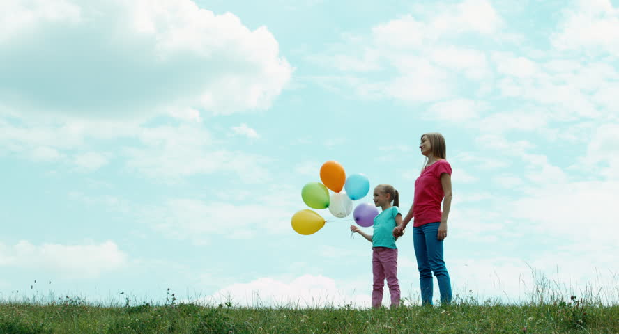 Happy family against the sky looking into the distance. Child holding balloons. Mother and daughter with balloons looking at camera | Shutterstock HD Video #10613405