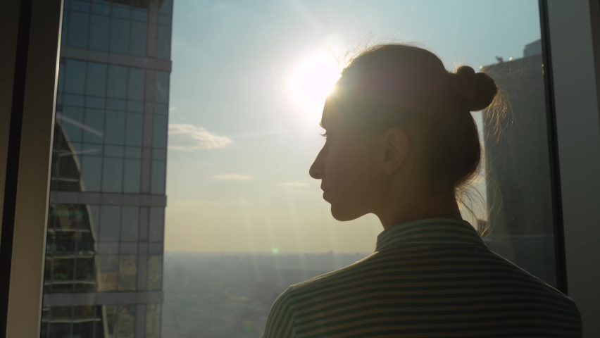 Success, opportunity, sightseeing, discover and future concept. Back view of pensive woman silhouette looking at cityscape through window of skyscraper. Summer time, sun lens flare, daylight | Shutterstock HD Video #1061344615