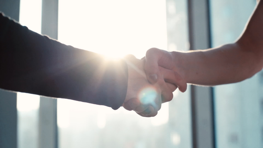 Close-up of two business partners shaking hands with each other to signify an agreement in the office against the background of the window and sunlight. Tracking shot in slow motion.