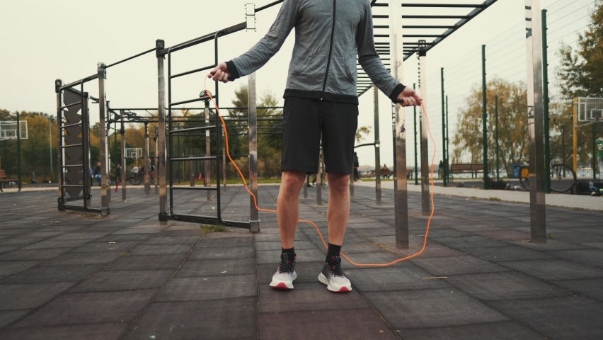 Sporty man jumping with skipping rope workout outdoor. Man use skipping rope. Cardio workout at outside gym. Sports beginner practicing basic jumps with skipping rope. Exercises for fast weight loss. Royalty-Free Stock Footage #1061347156