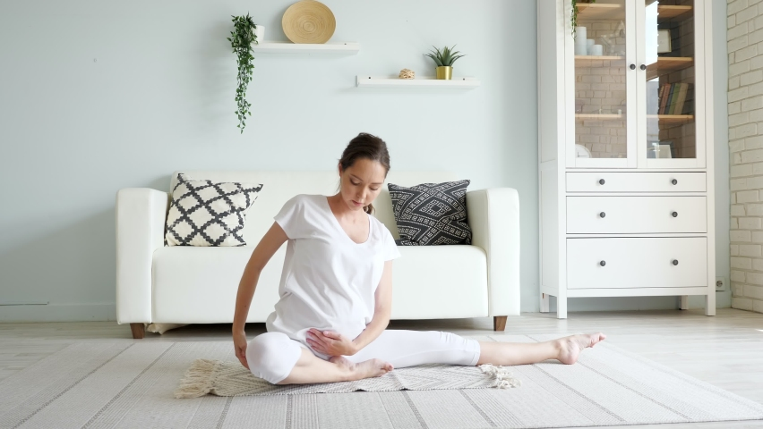 Pregnant woman in white clothes does yoga sitting on floor with rug against designer sofa at home   Shutterstock HD Video #1061353882