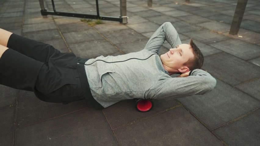 Man doing exercises on foam roller outdoor. Male stretching his back over vibrating foam roller for physical therapy. Health, injury concept. Massager for relaxation, stretching muscles and back pain.   Shutterstock HD Video #1061355769