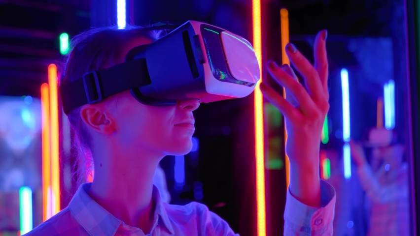 Slow motion: woman using virtual reality headset and looking around at interactive technology exhibition with colorful illumination. VR, futuristic, retrowave, immersive, entertainment concept | Shutterstock HD Video #1061357203