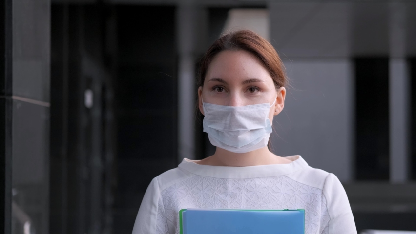 A masked business woman walks next to the company building. Work during epidemic | Shutterstock HD Video #1061358133