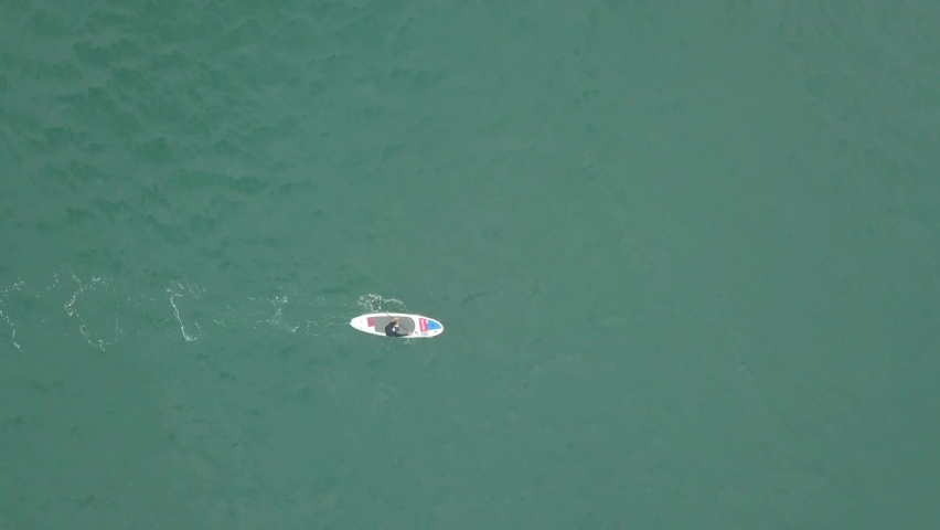 Aerial view with paddleboarder advancing while standing on his board. Tracking   Shutterstock HD Video #1061360815