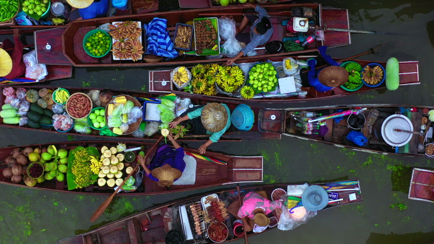Aerial view famous floating market in Thailand, Damnoen Saduak floating market, Farmer go to sell organic products, fruits, vegetables and Thai cuisine, Tourists visiting by boat, Ratchaburi, Thailand | Shutterstock HD Video #1061362276