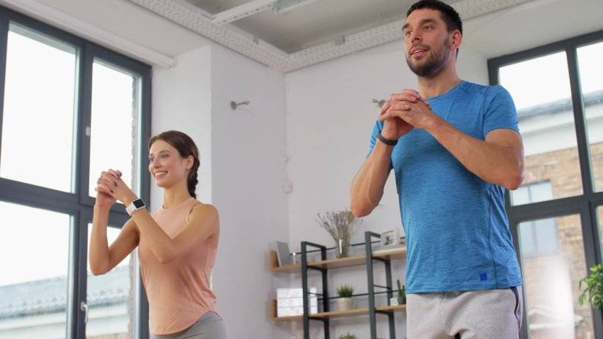 Sport, fitness, lifestyle and people concept - smiling man and woman exercising and doing squats in low lunge at home   Shutterstock HD Video #1061365603