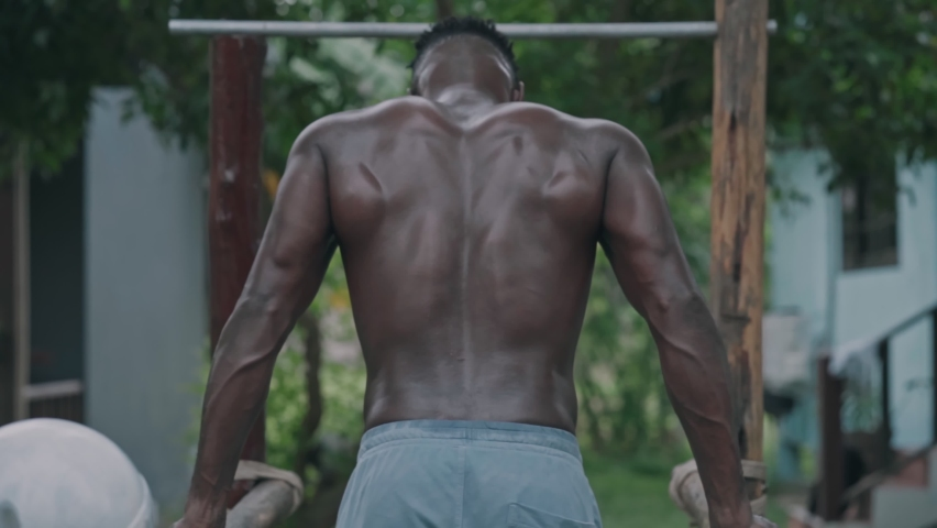 Young african american fit man doing dips on parallel bars at an outdoor gym park   Shutterstock HD Video #1061366839