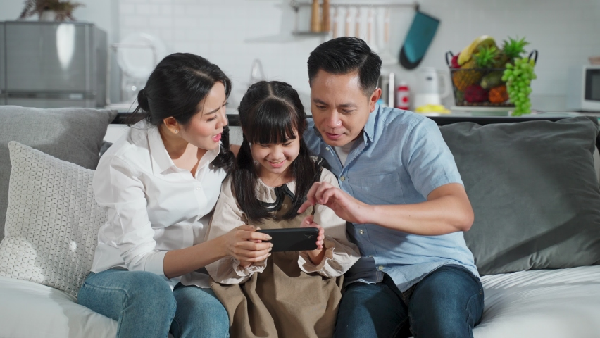 Asian family kid, mother, father playing game on smartphone together in living room at home with happiness and smile. Happy activity technology lifestyle mobile phone use concept. | Shutterstock HD Video #1061367538