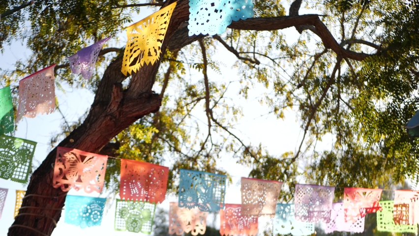Colorful mexican perforated papel picado banner, festival colourful paper garland. Multi colored hispanic folk carved tissue flags, holiday or carnival. Authentic fiesta decoration in Latin America. Royalty-Free Stock Footage #1061368714