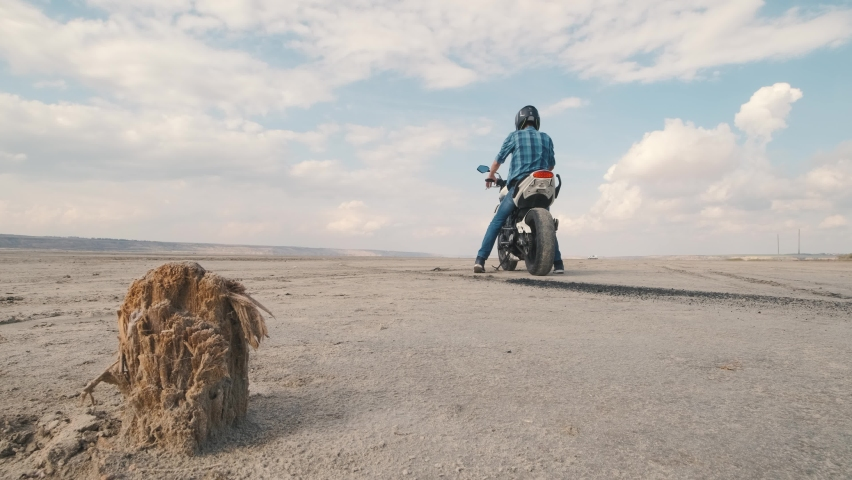 Motorcyclist doing tire burnout in the desert, slow motion. Professional motorcyclist drift on sport bike on a dry salt lake and ride away   Shutterstock HD Video #1061370121