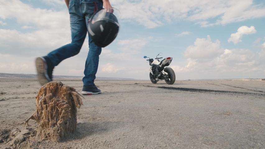 Motorcyclist doing tire burnout in the desert, slow motion. Professional motorcyclist drift on sport bike on a dry salt lake and ride away   Shutterstock HD Video #1061370130