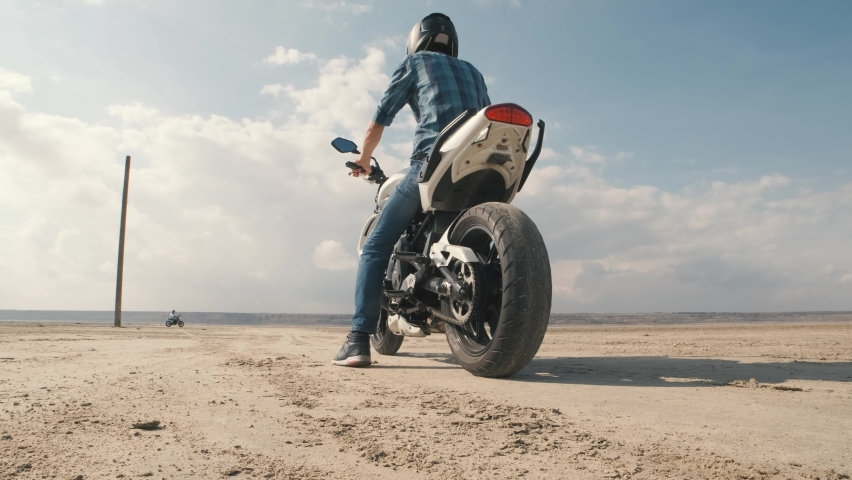 Motorcyclist doing tire burnout in the desert, slow motion. Professional motorcyclist drift on sport bike on a dry salt lake and ride away   Shutterstock HD Video #1061370133