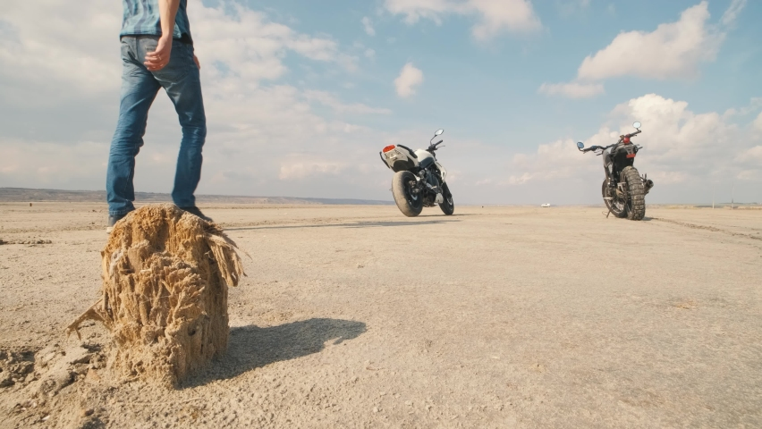 Motorcyclist doing tire burnout on customized motorcycle in the desert, slow motion. Professional motorcyclist drift on sport bike on a dry salt lake and ride away   Shutterstock HD Video #1061370205