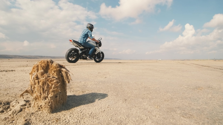 Motorcyclist doing tire burnout on customized motorcycle in the desert, slow motion. Professional motorcyclist drift on sport bike on a dry salt lake and ride away   Shutterstock HD Video #1061370208