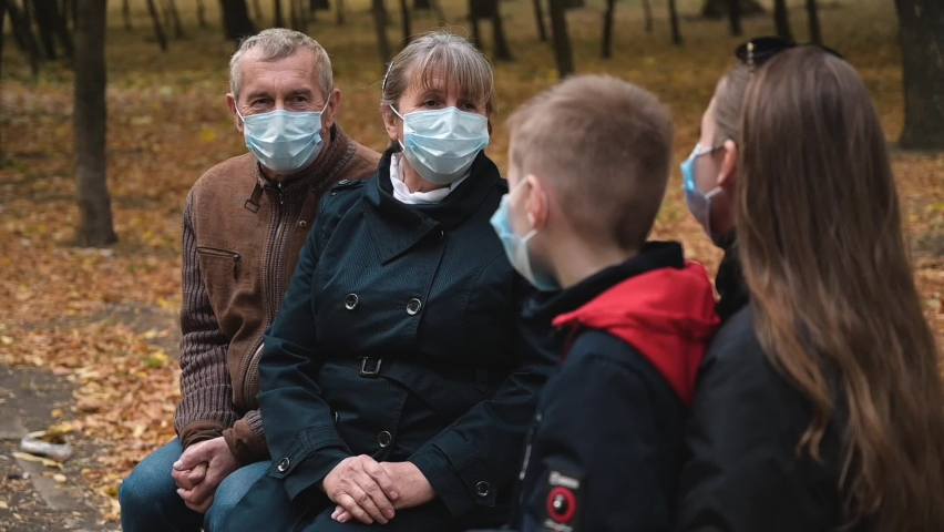 Social distance. Elderly couple talk in a park with their daughter and grandson wearing medical masks during a short meeting. During the second wave of the Covid-19 pandemic. Safety in public places. Royalty-Free Stock Footage #1061373247