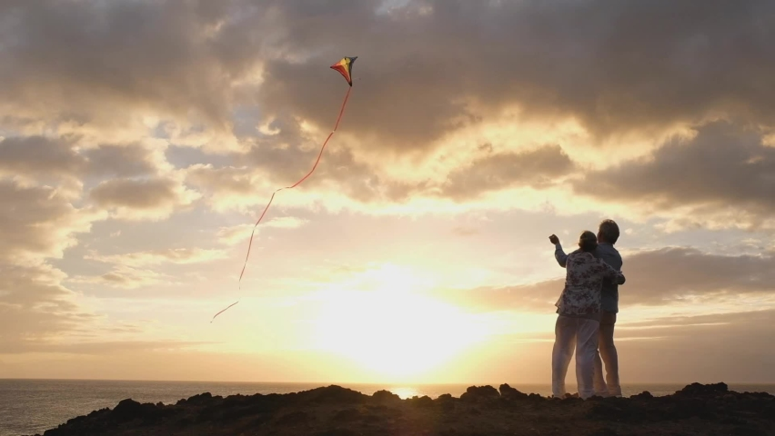 Silhouette of a couple of people and mature seniors outdoors playing with a kite at the beach enjoying summer and vacations   Shutterstock HD Video #1061377072