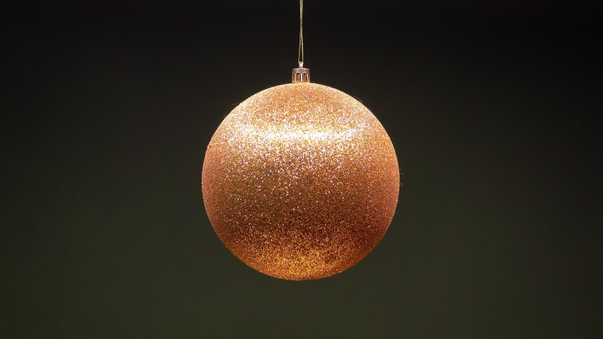 Golden Christmas ball toy turning round and back in luminous light on dark green background. New Year pattern. | Shutterstock HD Video #1061380687