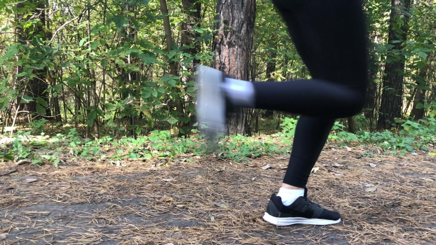 A woman runs through the autumn forest during the day slow motion.   Shutterstock HD Video #1061384641