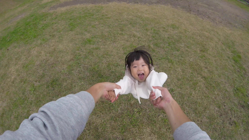 Running asian toddler girl comes and dad hands holding spinning little happy smiling cute daughter playing together at playground in residential area POV shot carefree family enjoying weekend relaxing   Shutterstock HD Video #1061385793
