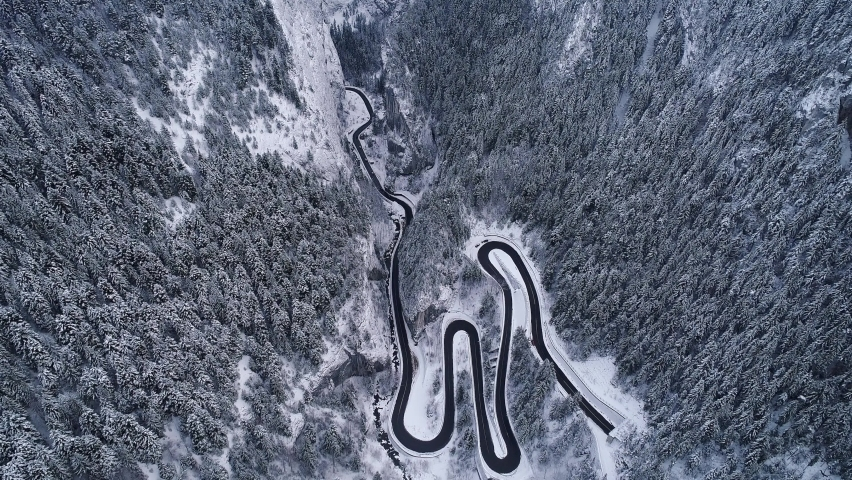 Aerial drone 4K footage of a curved windy road motorway through mountains next to a river in winter landscape in Romania - Bicaz Gorges