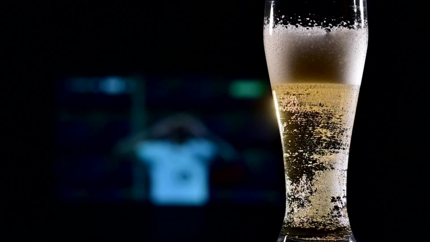 Close-up of fresh foaming light beer in a glass and football on TV on background. Sports bar concept   Shutterstock HD Video #1061386933