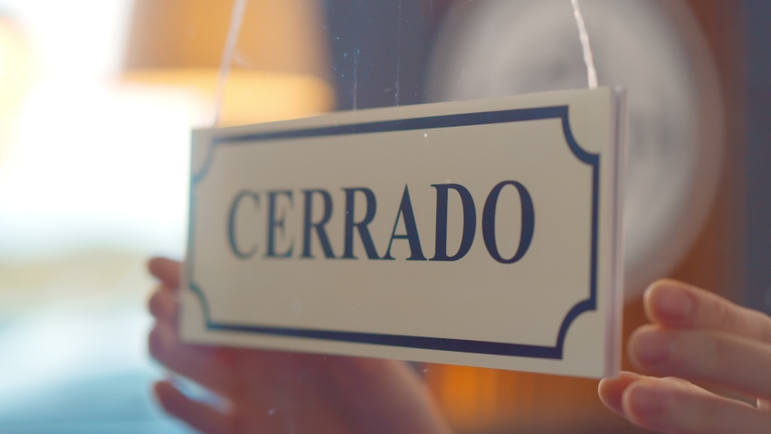 Close up of human turning abierto cerrado sign hanging on glass door of spanish cafe. Owner or seller turning open closed sign written in spanish on window of store