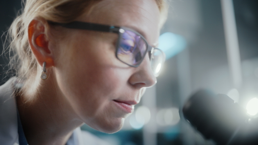In Bright Medical Science Laboratory: Beautiful Microbiologist Wearing Glasses Looks Under Microscope Analyzing Sample. Brilliant Scientist, working with High-Tech Equipment. Macro Close-up Shot