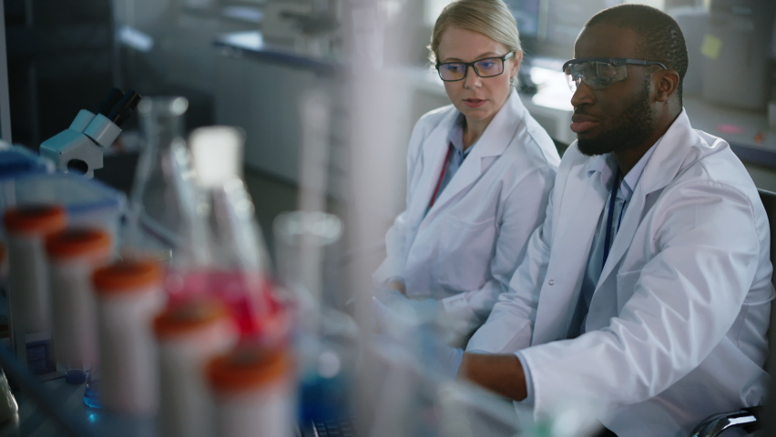 Bright Medical Science Laboratory with Diverse Team of Research Scientists Working. Microbiologist Looks Under Microscope Talks to Biochemist Using Laptop. High-Tech Equipment. Slow Motion Dolly Shot Royalty-Free Stock Footage #1061389486