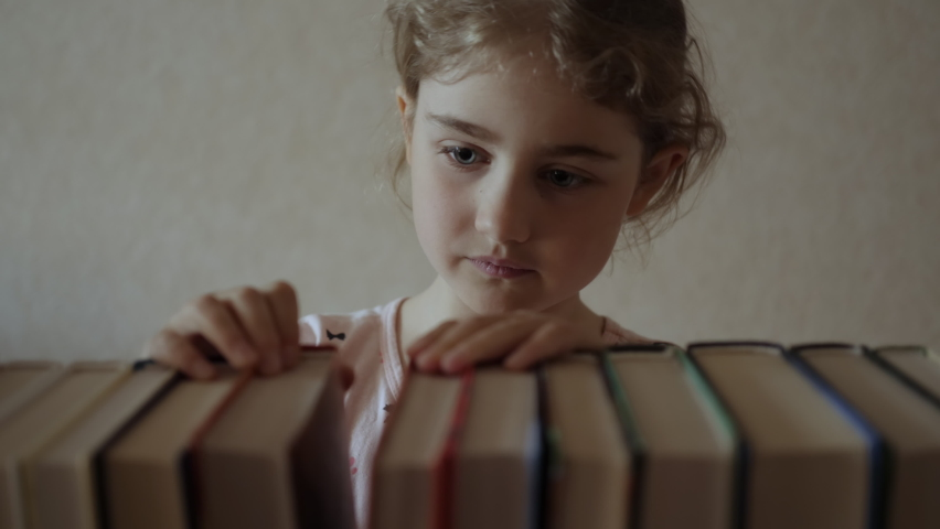 Little Girl Child Choose Books on Shelf. Young Schoolgirl in Glasses Taking Books From Shelf and Flipping Through Pages in Library.  Book Reading Hobby. Royalty-Free Stock Footage #1061394889