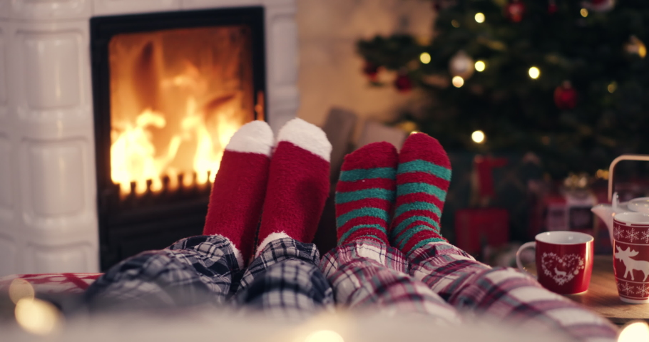 Couple feet in cozy christmas woolen socks near fireplace with decorated xmas tree and tee cup in background shot in 4k | Shutterstock HD Video #1061408821