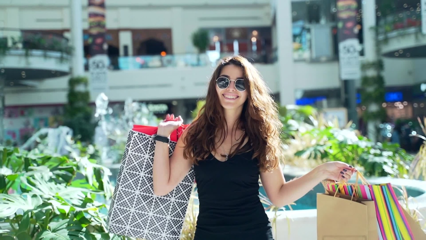 Portrait of cheerful young shopaholic woman holding paper bags with purchases and smiling at camera standing on shopping center. Happy lady shopping on black friday joyfully jumps for joy