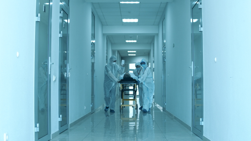 Group of doctors are taking a patient through the clinic hall Royalty-Free Stock Footage #1061416060