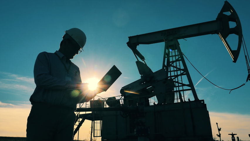 Silhouette of an oil worker and an oil pump. Oil industry, crude oil prices concept.