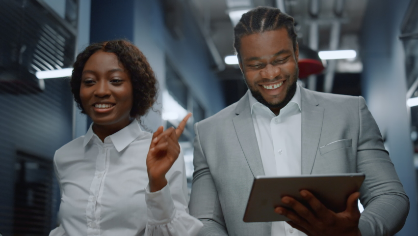 Closeup african american colleagues walking in business center. Positive afro business couple discussing plan on tablet computer in office. Successful business people working on the go in corridor Royalty-Free Stock Footage #1061418457
