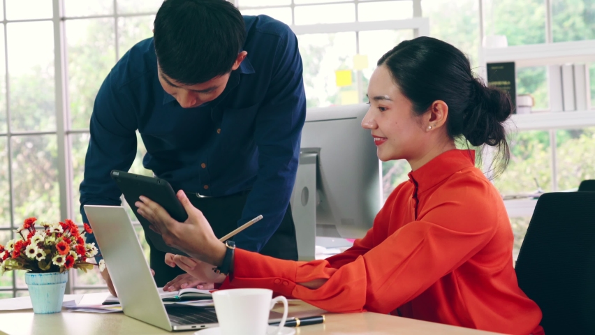 Two business people talk project strategy at office meeting room. Businessman discuss project planning with colleague at modern workplace while having conversation and advice on financial data report. | Shutterstock HD Video #1061420119