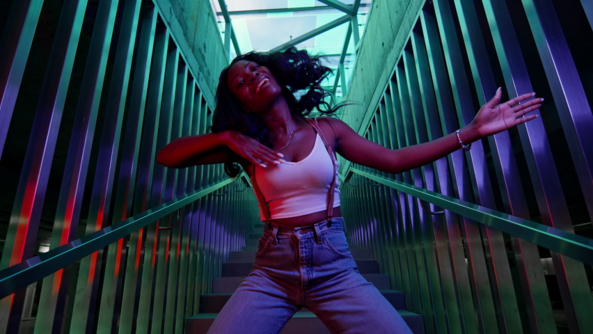 Girl Dancer Dancing On The Stairs. Black Young Girl Moves Rhythmically. She Has Long Black Hair. Pretty Dancer. Facial Expressions Of The Girl Change Guickly. Lighting Creates Blue And Green Colors Royalty-Free Stock Footage #1061421037
