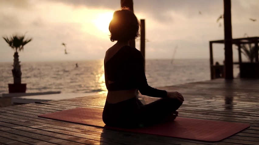 Yogi girl is sitting in lotus pose in front the sea in summer on sunset, healthy lifestyle, movement concept, meditation concept Royalty-Free Stock Footage #1061430130