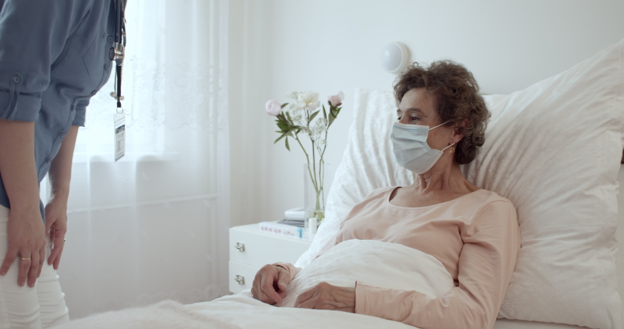 Elderly Woman Wearing Protection Face Mask Having Friendly Communication With Nurse in Hospital Room. Home Caregiver With Face Mask Holding Hands of Female Senior Patient Lying in Bed at Nursing Home.
