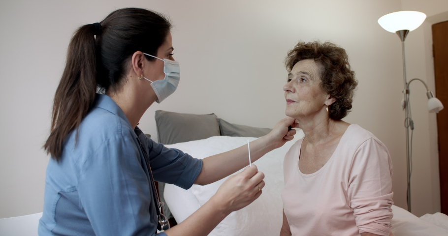 Nurse Swabbing Nose of Senior Female Patient for Coronavirus Test. Elderly Woman Sitting on Hospital Bed Having Her Nasal Swab for Covid-19 Done. Royalty-Free Stock Footage #1061436223