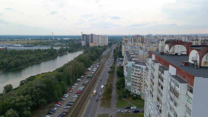 Aerial view of traffic on a street, a river and apartment buildings, in a old soviet district, overcast day, in Kiev city, Ukraine - dolly, drone shot | Shutterstock HD Video #1061438761