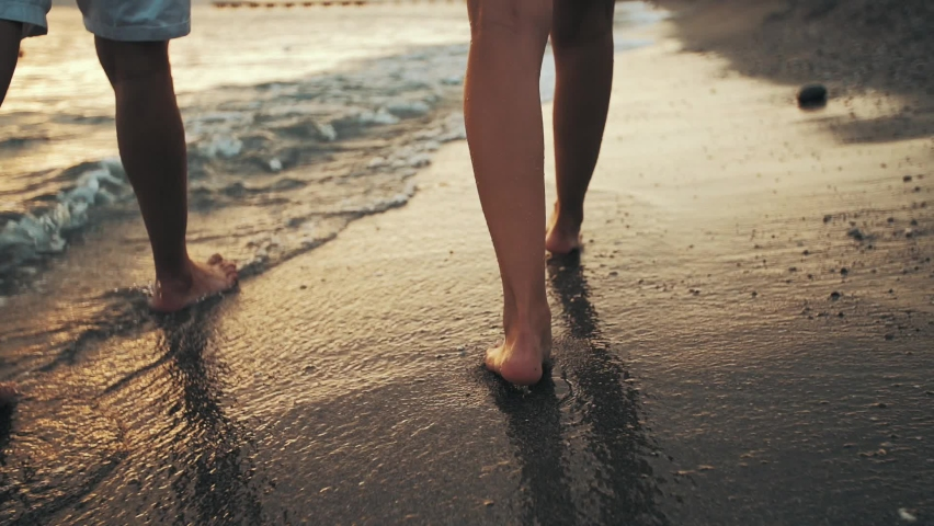 couple walks on the beach at sunset. The camera only takes the legs of the couple walking along the sea shore. Royalty-Free Stock Footage #1061439904