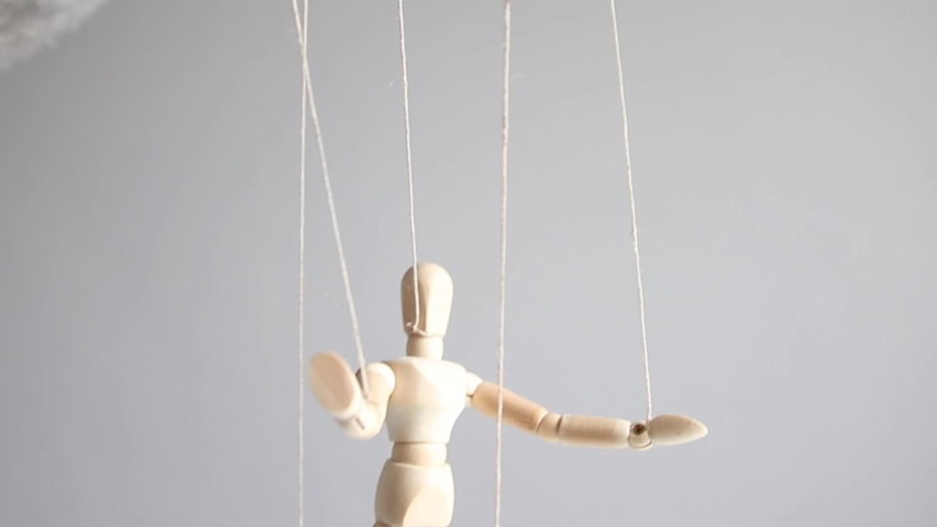 Human wood figure with threads suspended in the air on gray background. Manipulation, addiction concept. | Shutterstock HD Video #1061449291