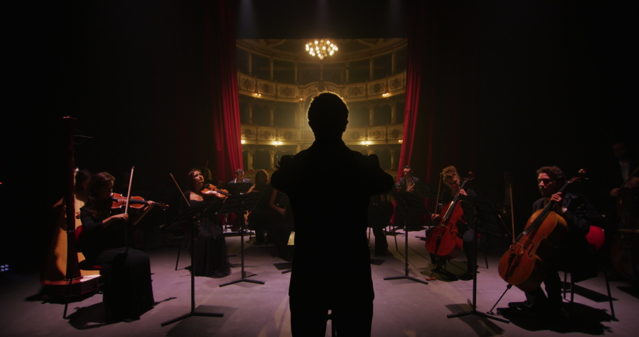 Cinematic shot of conductor directing symphony orchestra with performers playing violins, cello and trumpet on classic theatre with curtain stage during music concert with dramatic lights. Royalty-Free Stock Footage #1061452282
