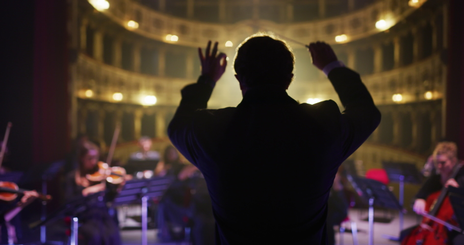 Cinematic shot of conductor directing symphony orchestra with performers playing violins, cello and trumpet on classic theatre with curtain stage during music concert with dramatic lights. Royalty-Free Stock Footage #1061452291