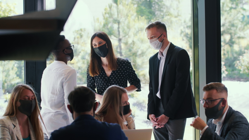 Group of happy young smiling business people talking, working at modern office, all wearing COVID-19 safety face masks.