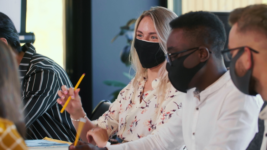 Business after coronavirus crisis. Close-up happy smiling multiethnic young managers work at office table in face masks.